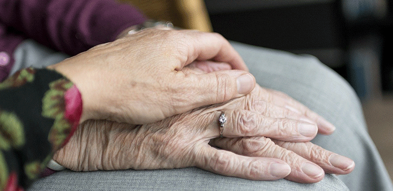 a lady holding hands with an elderly relative