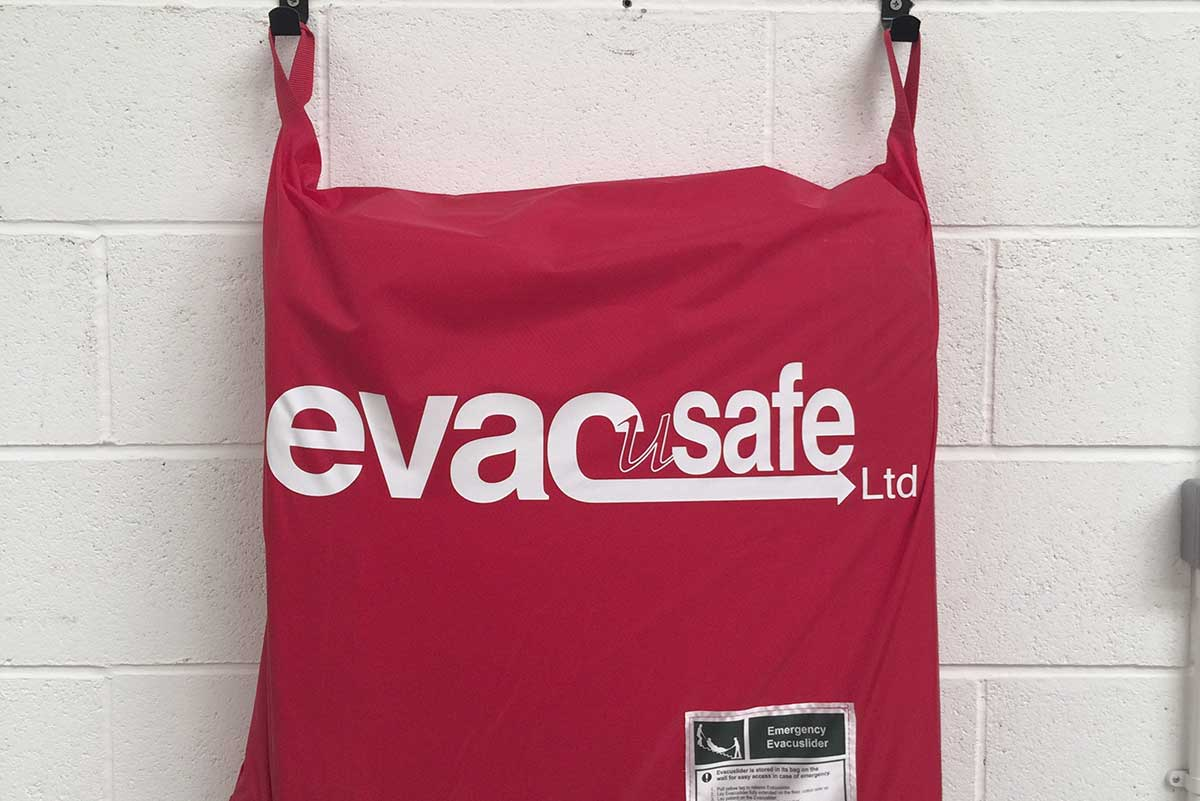 Evacuslider hanging from wall hooks in a zipped bag